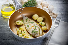 Sole fish with potatoes. Over casserole Royalty Free Stock Images