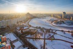 Sole luminoso che aumenta sopra la città sul primo mattino di inverno fotografia stock libera da diritti