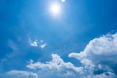 Sole luminoso con i chiarori e le nuvole del sole sul chiaro fondo del cielo blu, concetto caldo di estate Fotografia Stock