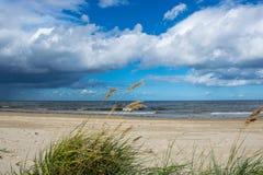 Sole luminoso e nuvole di pioggia scure sopra il Mar Baltico fotografia stock