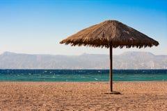 Sole sunshade on a beach. Single sunshade near coast of the Read Sea in Aqaba, Jordan stock photography