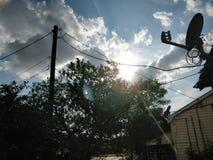 Soleggiato, vista degli alberi e foglie verdi Con un mazzo di nuvole e di luce sopra le case Immagini Stock