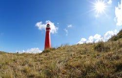 Soleil au-dessus de phare rouge Photographie stock libre de droits