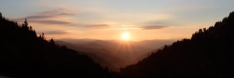 Soleil au-dessus de vallée de montagne - panorama images stock