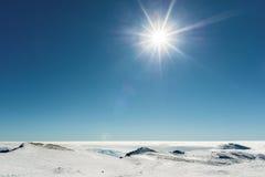 Soleil au-dessus des montagnes neigeuses Photographie stock libre de droits