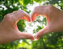 Soleil 2 de coeur d'amour de mains Photographie stock libre de droits