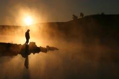 Soleil de matin et randonneur silhouetté par bordure de brouillard sur le lac calme Image libre de droits