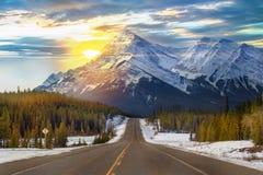 Soleil jetant un coup d'oeil au-dessus d'une route de montagne images libres de droits