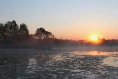 Soleil Levant au-dessus du lac Couleurs tendres de brume Images stock
