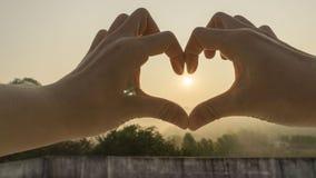 Soleil Levant avec des mains d'amour Images stock