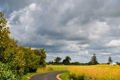 Soleil lumineux et grands nuages de pluie au-dessus de la route au Danemark photographie stock libre de droits
