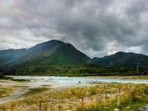 Soleil sur la rivière avec les nuages foncés Image libre de droits