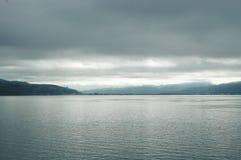 Soleil traversant un ciel orageux pour tomber sur un lac argenté image libre de droits