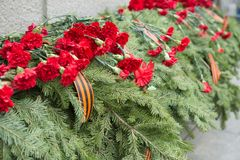 Solemn funeral coniferous garland with carnation flowers and St. George ribbon. Solemn funeral coniferous garland with carnation flowers and St. George ribbon stock images