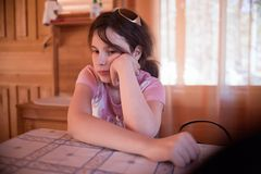 Solemn girl at table Stock Photos