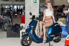 Solemn opening of the salon for the sale of automobiles, Firm `Nizhegorodets.`Young girl model posing near an electric scooter. royalty free stock photography