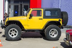Solemn opening of the salon for the sale of automobiles. Jeep `Wrangler Rubicon` with large out-of-road wheels, Yellow. royalty free stock photo