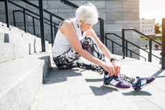 Solemn senior lady getting ready for exercise on block stairs Stock Images