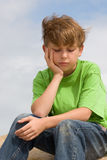 Solemn Thoughts. A downcast child sitting and thinking Royalty Free Stock Photography