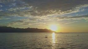 Solen för den flyg- sikten stiger bakifrån kullar på horisont ovanför havet lager videofilmer