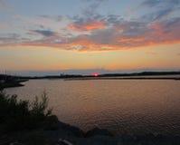 Solen faller bak sjön royaltyfri foto