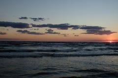 Solen faller in i havet Fotografering för Bildbyråer