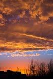 Solen går ner över det stads- landskapet Arkivfoto