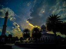 Solen går ner bak masjiden royaltyfri fotografi