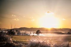 Solen går ner i berg Arkivbild