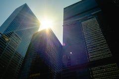 Solen passerar mellan i stadens centrum kontorstorn arkivfoto