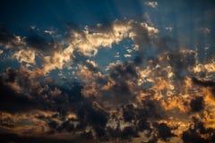 Solen rays göra deras väg till och med trasiga fluffiga moln arkivbild