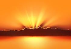 Solen rays till och med molnen i solnedgången royaltyfri bild