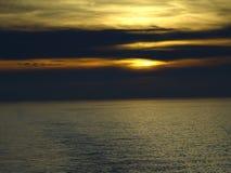 Solen sjunker i havet royaltyfria bilder