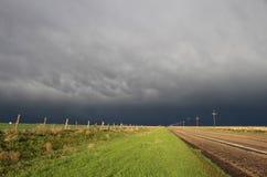 Solen skiner ljust efter en hällregn, med en storm i avståndet Arkivfoto