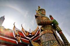 Solen skiner till och med taket av en tempel och en thailändsk jätte som bevakar en tempel i Bangkok, Thailand Royaltyfri Bild
