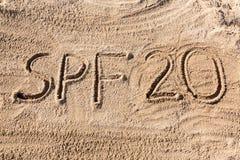 Solen skyddar begrepp för faktor tjugo Ord för SPF som 20 är skriftligt på stranden arkivfoto