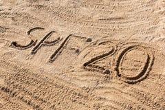 Solen skyddar begrepp f?r faktor tjugo Ord f?r SPF som 20 ?r skriftligt p? stranden royaltyfria bilder
