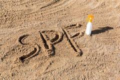Solen skyddar faktor Spf-ord som ?r skriftligt p? sanden och den vita flaskan med solbr?nnakr?m Bakgrund f?r begrepp f?r hudomsor royaltyfria bilder