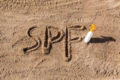 Solen skyddar faktor Spf-ord som ?r skriftligt p? sanden och den vita flaskan med solbr?nnakr?m Bakgrund f?r begrepp f?r hudomsor royaltyfri bild