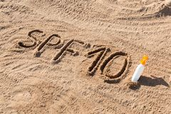 Solen skyddar faktor tio Ord för SPF som 10 är skriftligt på sanden och den vita flaskan med solbrännakräm Bakgrund för begrepp f arkivbilder