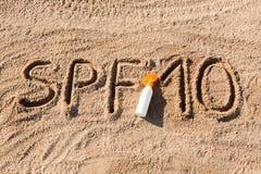 Solen skyddar faktor tio Ord f?r SPF som 10 ?r skriftligt p? sanden och den vita flaskan med solbr?nnakr?m Bakgrund f?r begrepp f royaltyfria foton