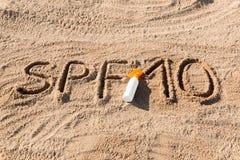 Solen skyddar faktor tio Ord f?r SPF som 10 ?r skriftligt p? sanden och den vita flaskan med solbr?nnakr?m Bakgrund f?r begrepp f royaltyfria bilder