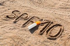 Solen skyddar faktor tio Ord f?r SPF som 10 ?r skriftligt p? sanden och den vita flaskan med solbr?nnakr?m Bakgrund f?r begrepp f royaltyfri fotografi