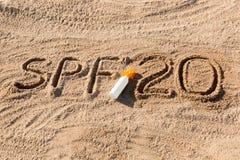 Solen skyddar faktor tjugo Ord f?r SPF som 20 ?r skriftligt p? sanden och den vita flaskan med solbr?nnakr?m Bakgrund f?r begrepp arkivbilder