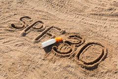 Solen skyddar faktor trettio Ord f?r SPF som 30 ?r skriftligt p? sanden och den vita flaskan med solbr?nnakr?m Bakgrund f?r begre arkivfoton
