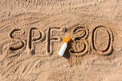 Solen skyddar faktor trettio Ord f?r SPF som 30 ?r skriftligt p? sanden och den vita flaskan med solbr?nnakr?m Bakgrund f?r begre royaltyfri foto