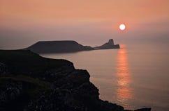 Solen som över ställer in, avmaskar huvudet, Rhossili Goweren, södra Wales Arkivfoton