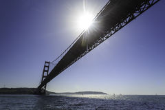 Solen som blockeras delvist av spännvidden, av Golden gate bridge, reflekterar på San Francisco Bay Royaltyfri Fotografi