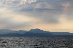 Solen som bryter till och med molnen över sjön Garda Italien royaltyfri fotografi