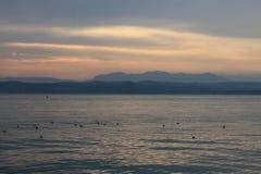 Solen som bryter till och med molnen över sjön Garda Italien royaltyfri bild